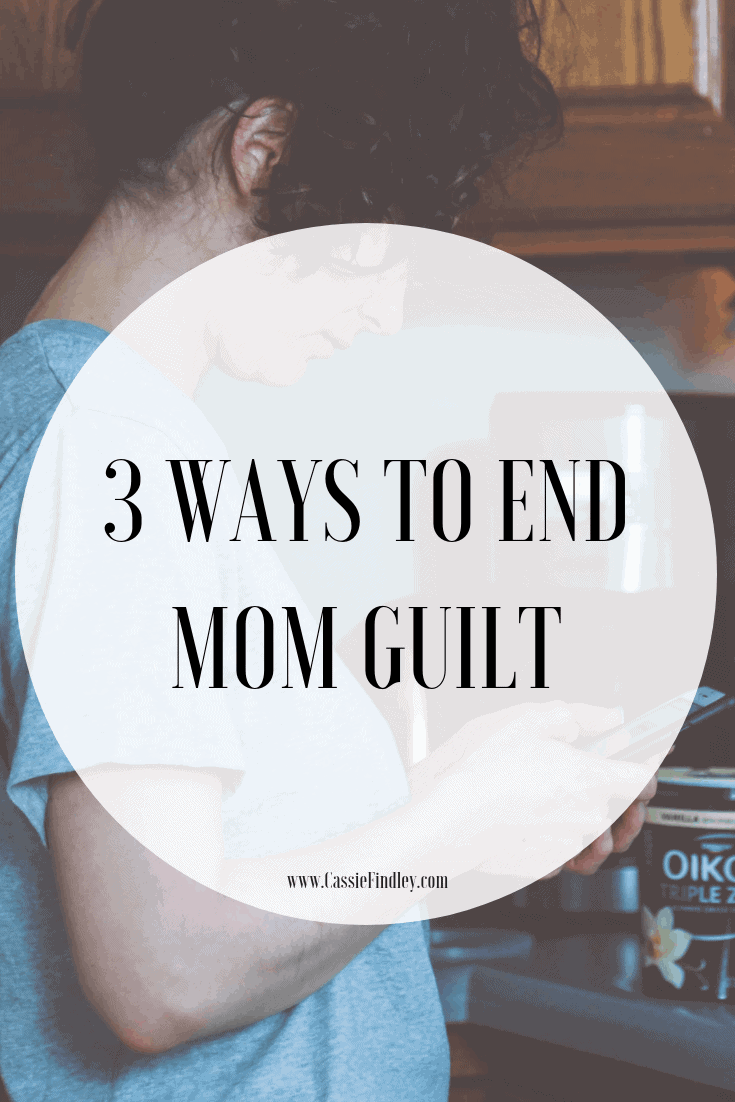 Picture of woman in kitchen on her phone with text overlay that says:3 Ways to End Mom Guilt